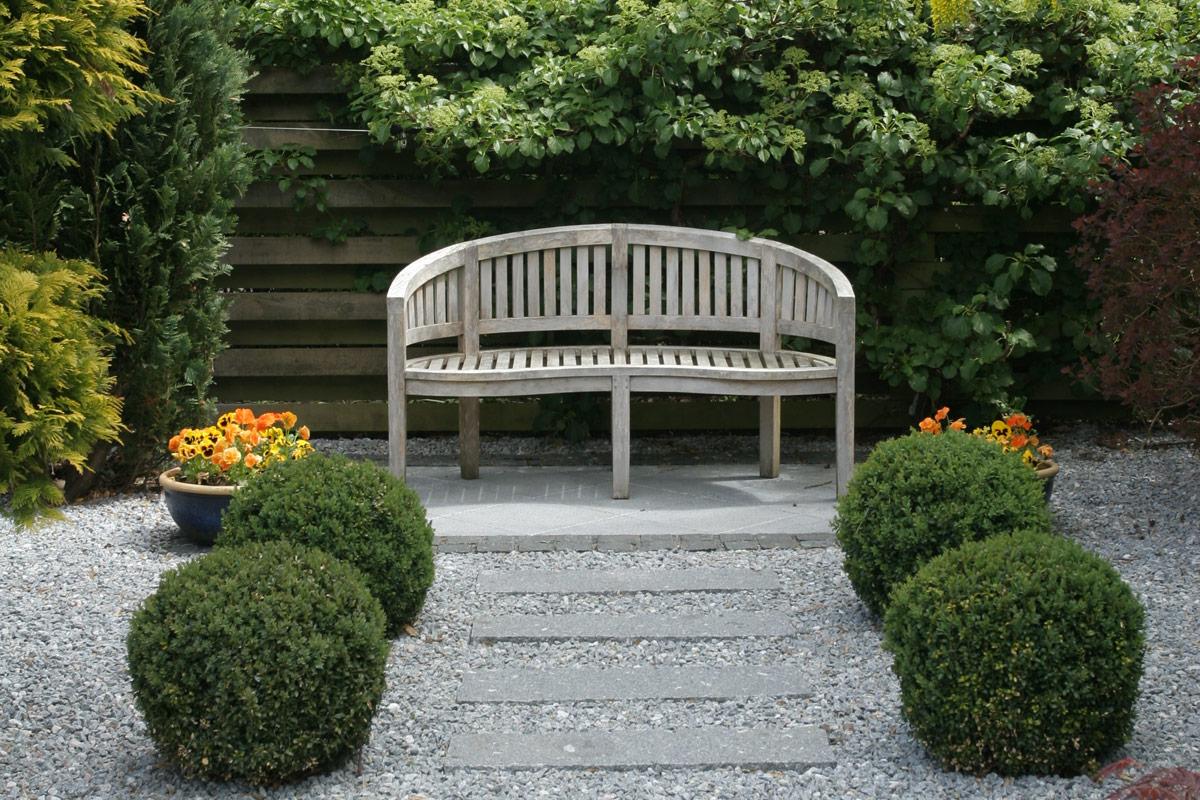Et-af-de-mange-rum-i-haven-med-romantisk-buet-træbænk